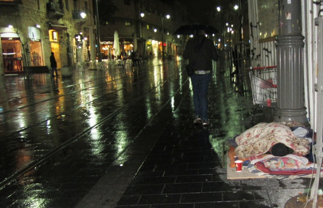 Jerusalem street in the rain, man sleeping on sidewalk