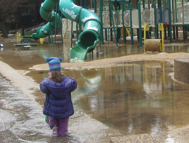 child splashing in puddles, flooding in Jerusalem