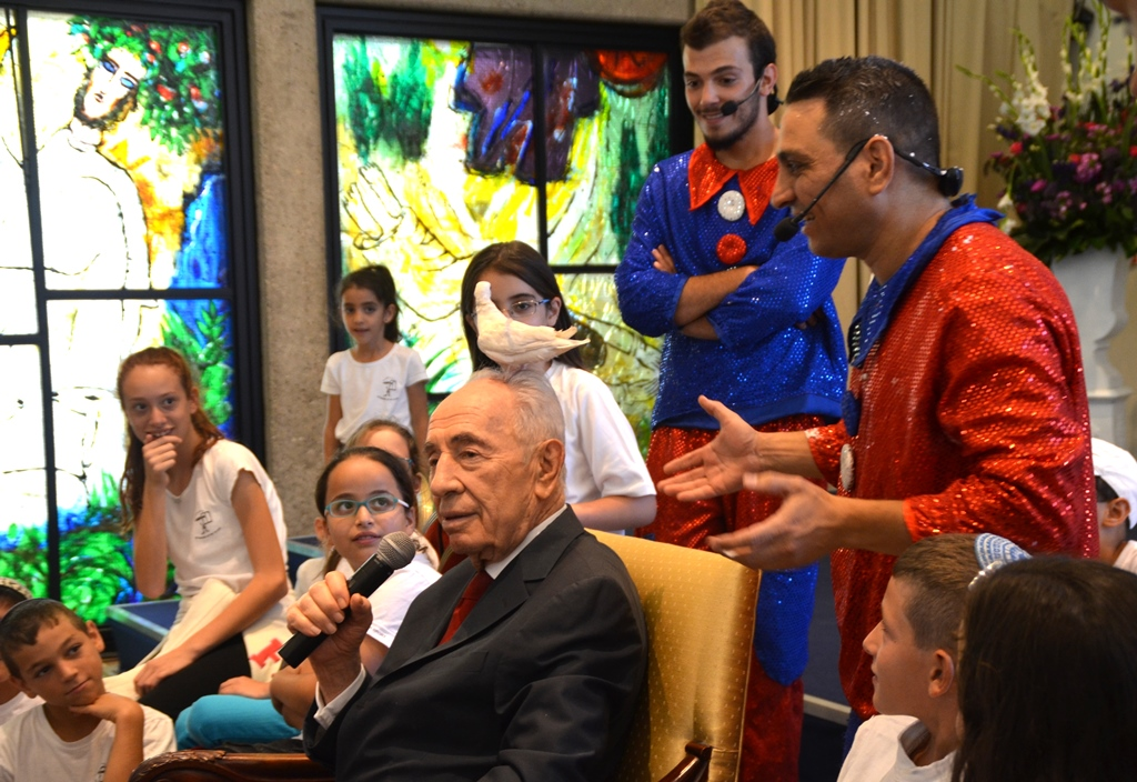 Performers at Beit Hanasi put dove on hear of President Shimon Peres